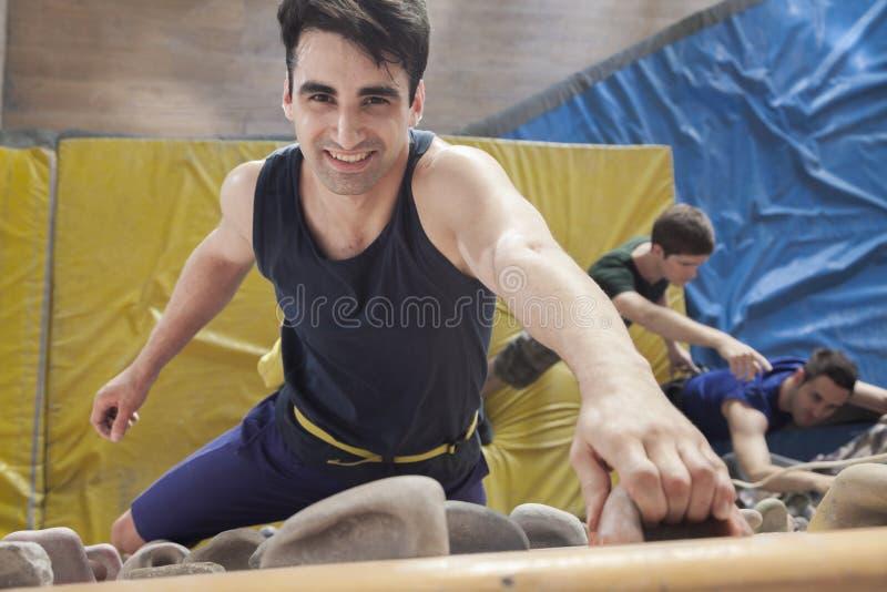 Homem novo de sorriso que escala acima uma parede de escalada em um gym de escalada interno, diretamente acima fotos de stock