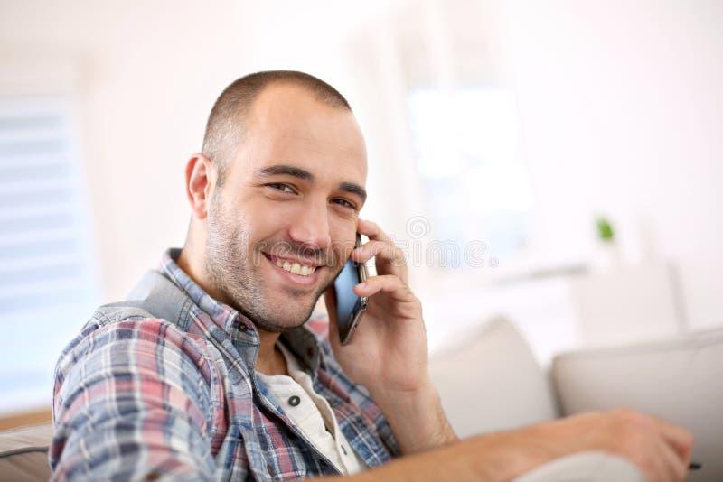Homem novo de sorriso que fala no telefone fotografia de stock