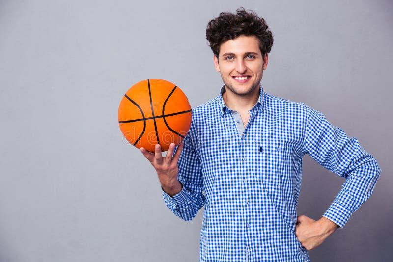 Homem novo de sorriso que guarda a bola da cesta fotografia de stock royalty free