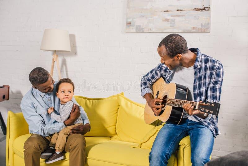 homem novo de sorriso que joga a guitarra e a vista do avô e do neto felizes imagens de stock