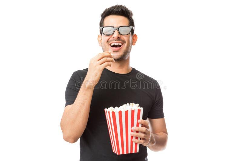 Homem novo de sorriso que olha o filme 3D ao comer a pipoca foto de stock