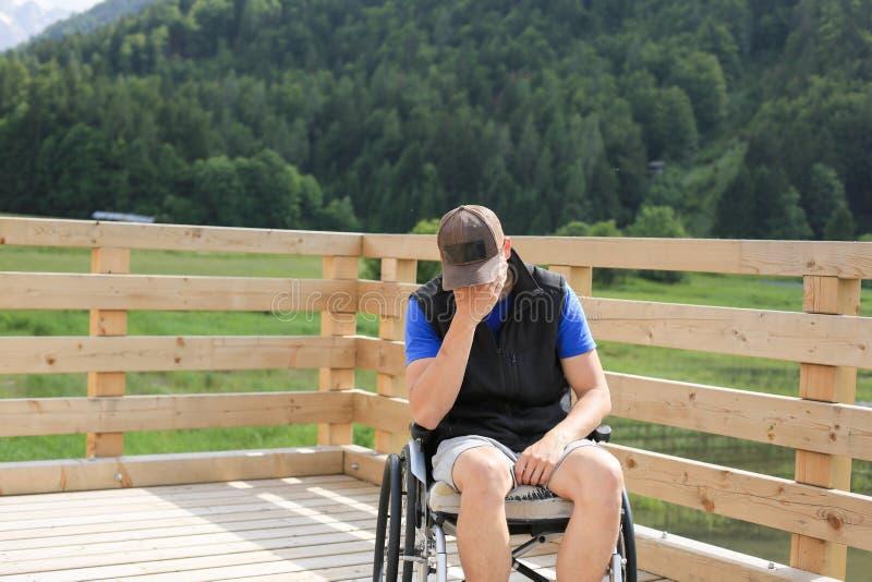 Homem novo deficiente em uma cadeira de rodas imagem de stock royalty free