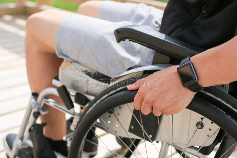 Homem novo deficiente em uma cadeira de rodas foto de stock