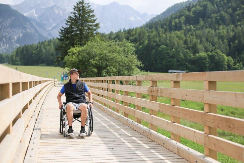 Homem novo deficiente em uma cadeira de rodas fotografia de stock