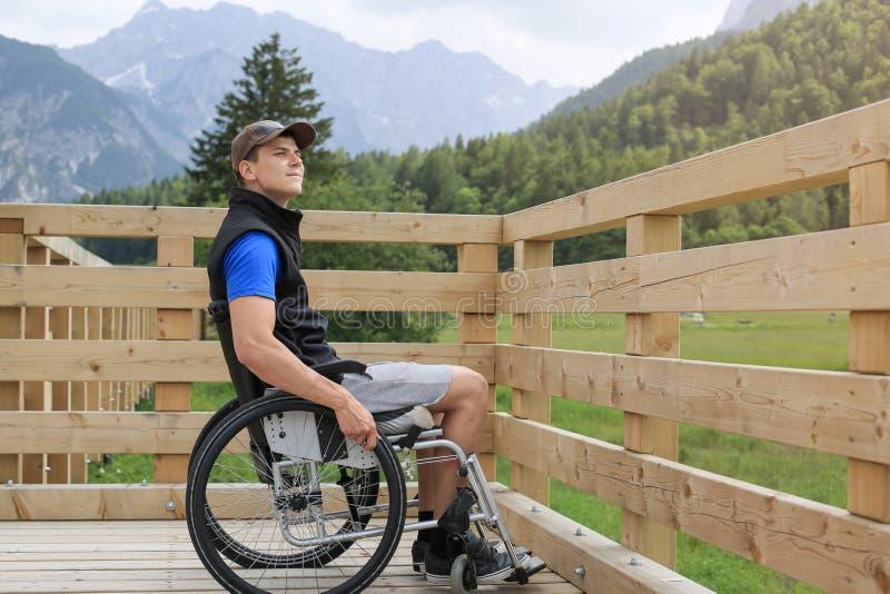 Homem novo deficiente em uma cadeira de rodas fotos de stock