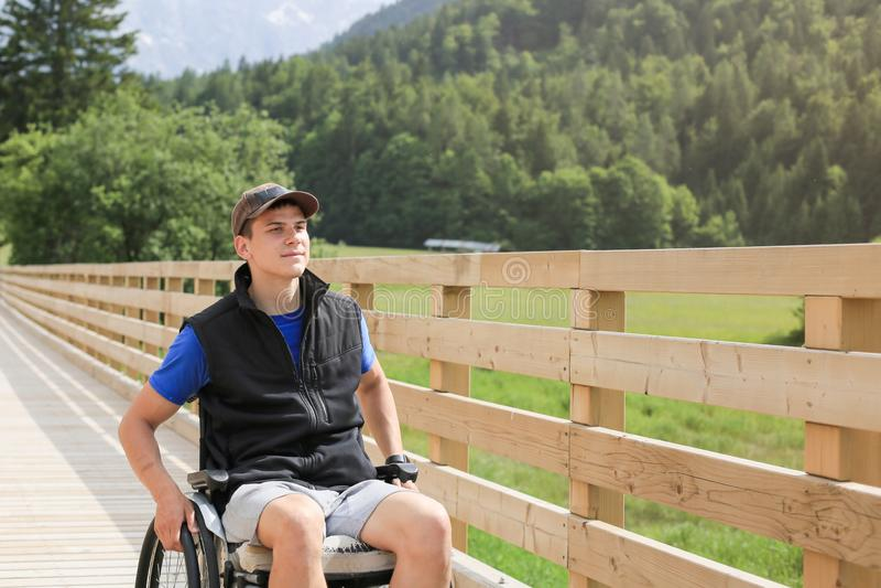 Homem novo deficiente em uma cadeira de rodas imagem de stock