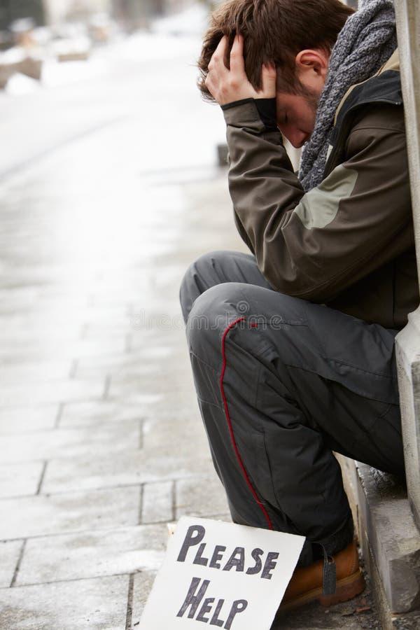 Homem novo desabrigado que implora na rua fotografia de stock