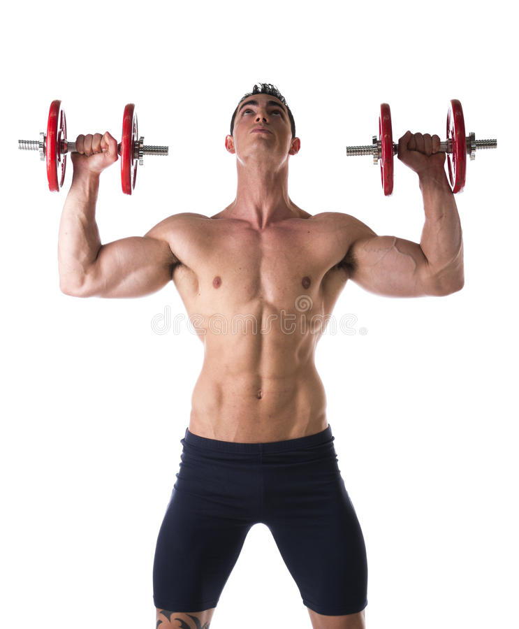 Homem novo descamisado muscular que exercita ombros com pesos fotografia de stock