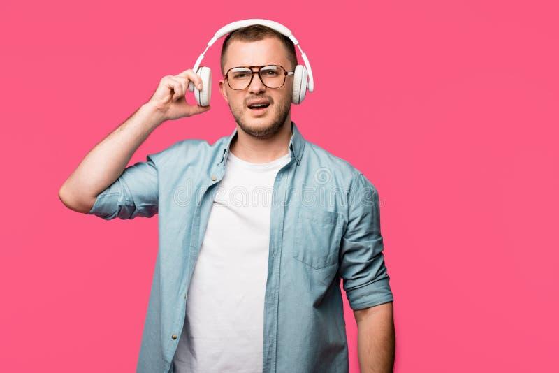 homem novo descontentado nos monóculos que vestem fones de ouvido e que olham a câmera isolada imagens de stock royalty free