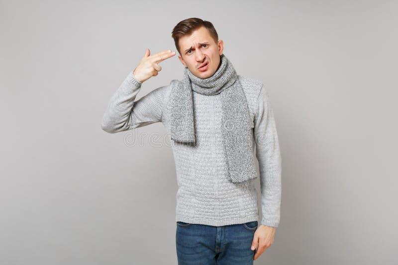 Homem novo desesperado na camiseta cinzenta, dedos do ponto do lenço a dirigir como se se dispara aproximadamente nno cinza imagem de stock