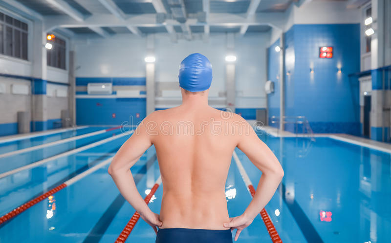 Homem novo desportivo na piscina que prepara-se para nadar, vista traseira fotografia de stock royalty free
