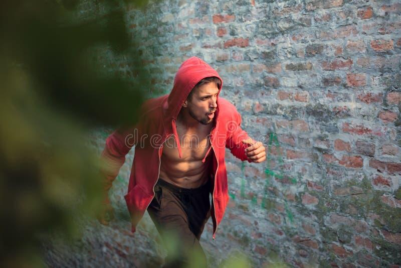 Homem novo determinado em uma camisa encapuçado vermelha que prepara-se para o exercício fotos de stock