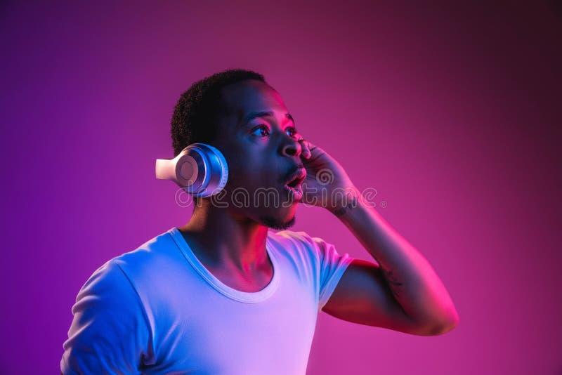 Homem novo do afro-americano que escuta a música na luz de néon imagens de stock