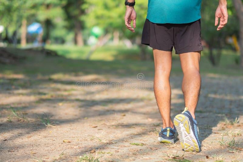 Homem novo do atleta que corre no parque exterior, no corredor masculino que movimentam-se na parte externa da estrada, na aptidã fotografia de stock royalty free