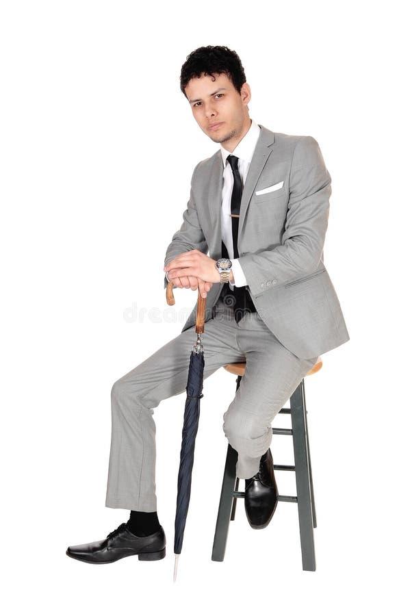Homem novo do bossiness que senta-se em um terno cinzento foto de stock