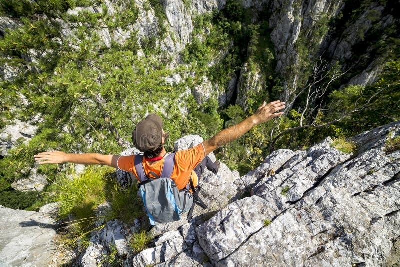 Homem novo do caminhante que estica seus braços na montanha fotos de stock royalty free