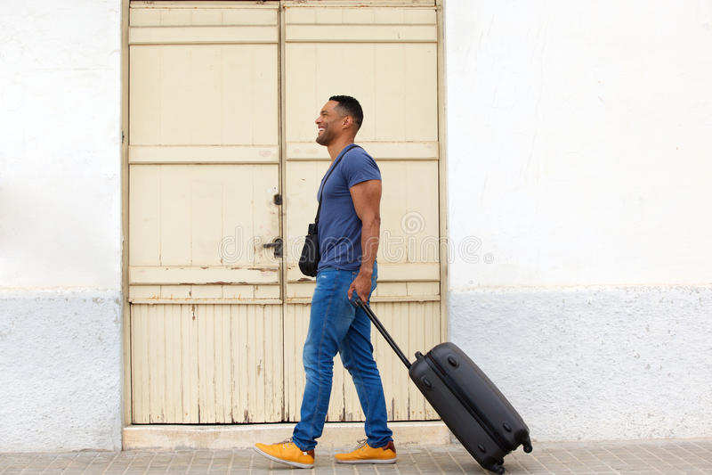 Homem novo do comprimento completo que viaja com mala de viagem fotografia de stock royalty free