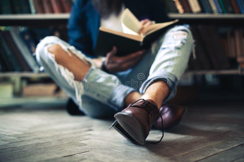 Homem novo do estudante que senta-se no assoalho, livro de leitura na biblioteca foto de stock