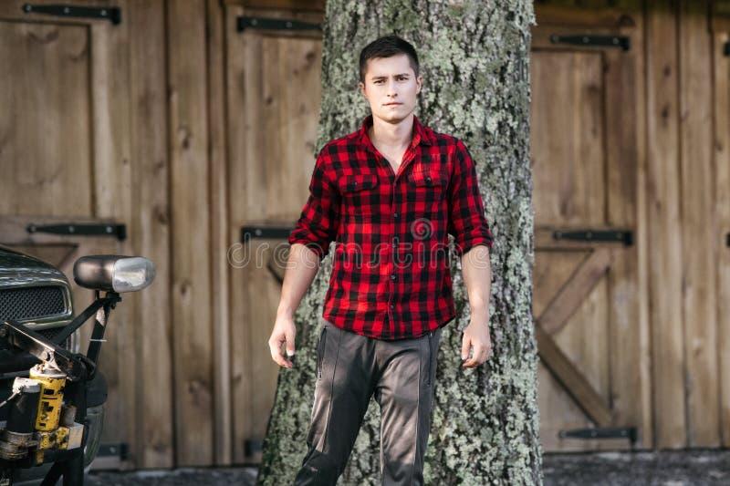 Homem novo do fazendeiro que anda no seu exploração agrícola perto do celeiro de madeira que veste o t-shirt vermelho foto de stock royalty free