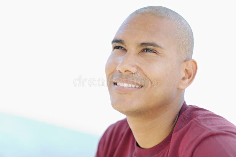 Homem novo do latino que sorri e que olha acima foto de stock royalty free