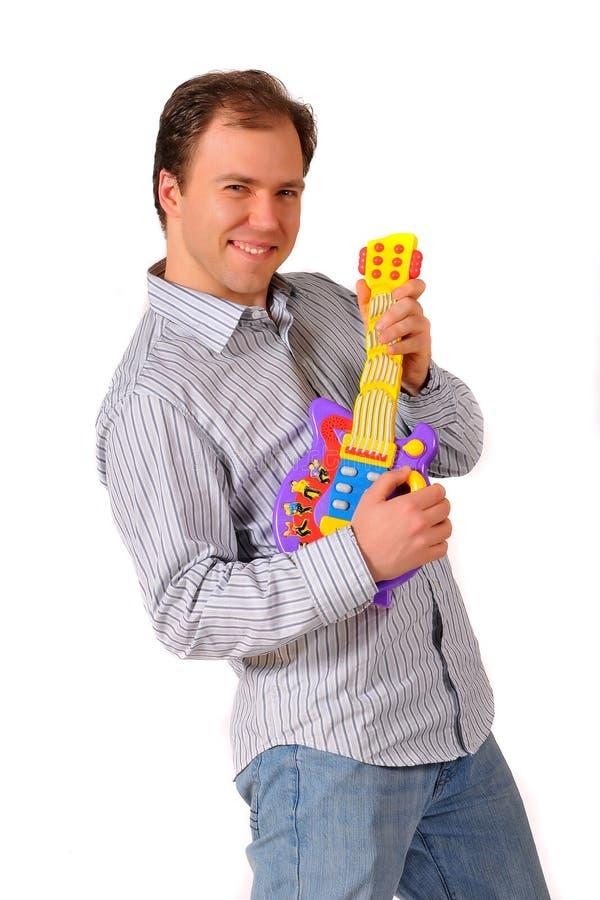 Homem novo do músico que joga a guitarra elétrica do brinquedo imagens de stock royalty free