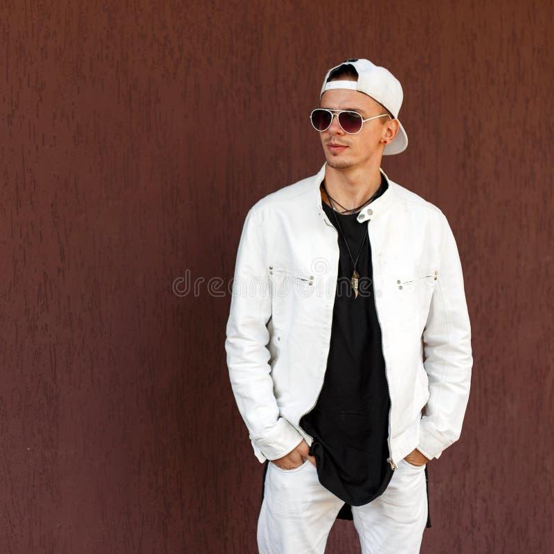 Homem novo do moderno agradável em um revestimento branco na moda do verão em um t-shirt preto à moda em um boné de beisebol eleg fotos de stock royalty free
