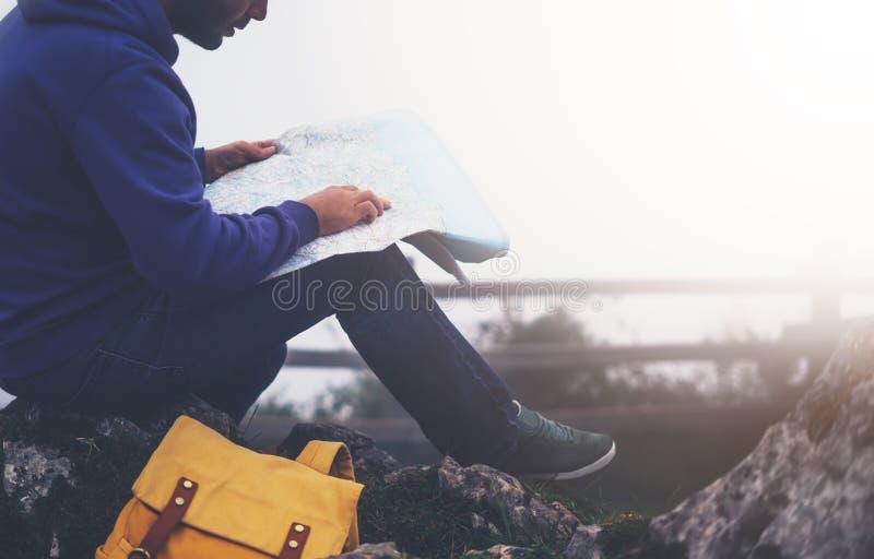 Homem novo do moderno com a trouxa que realiza nas mãos e que olha no mapa spain da montanha nevoenta, caminhante do viajante do  imagem de stock