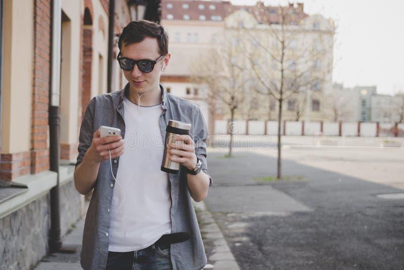 Homem novo do moderno que anda na rua e que usa seu smartphone fotografia de stock royalty free