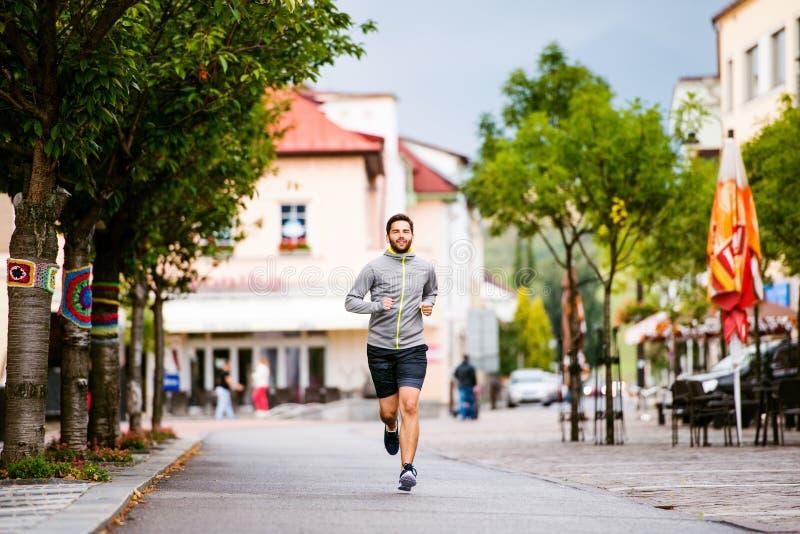 Homem novo do moderno que corre na cidade, rua principal fotos de stock