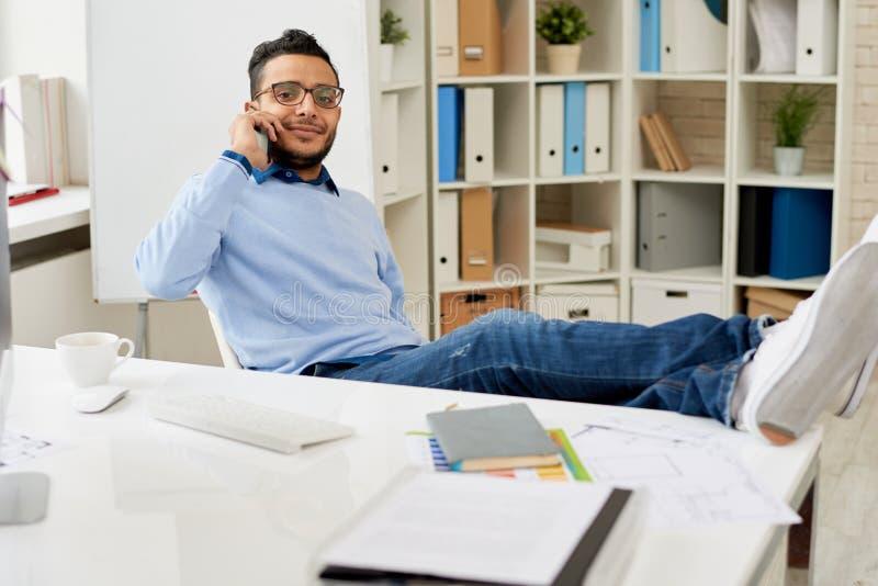 Homem novo do Oriente Médio que relaxa no local de trabalho fotos de stock
