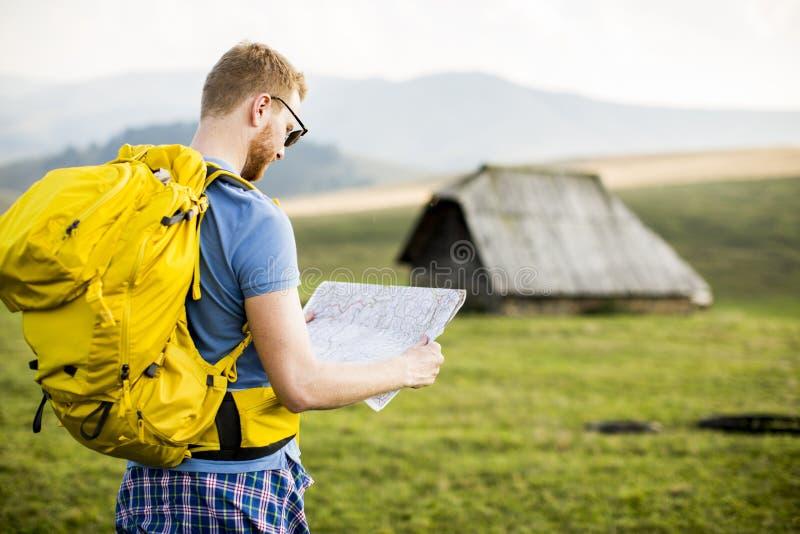 Homem novo do redhair na montanha que caminha guardando um mapa fotos de stock