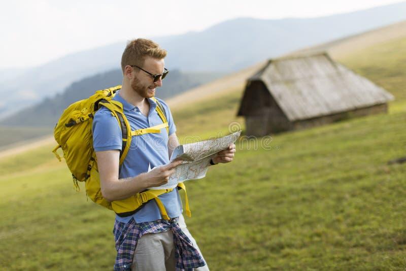 Homem novo do redhair na montanha que caminha guardando um mapa imagem de stock royalty free
