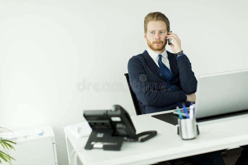 Homem novo do redhair que fala no telefone celular no escritório fotos de stock