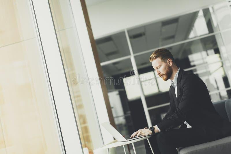 Homem novo do redhair que trabalha no escritório fotografia de stock