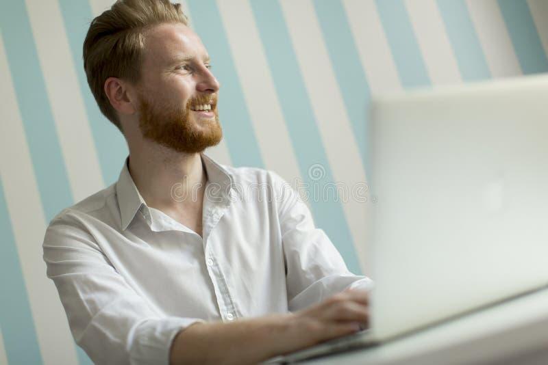 Homem novo do redhair que trabalha no portátil na sala pelo listrado azul foto de stock