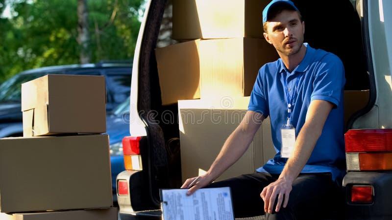 Homem novo do serviço de entrega que descansa, sentando-se na camionete, carregamento dos pacotes fotos de stock royalty free