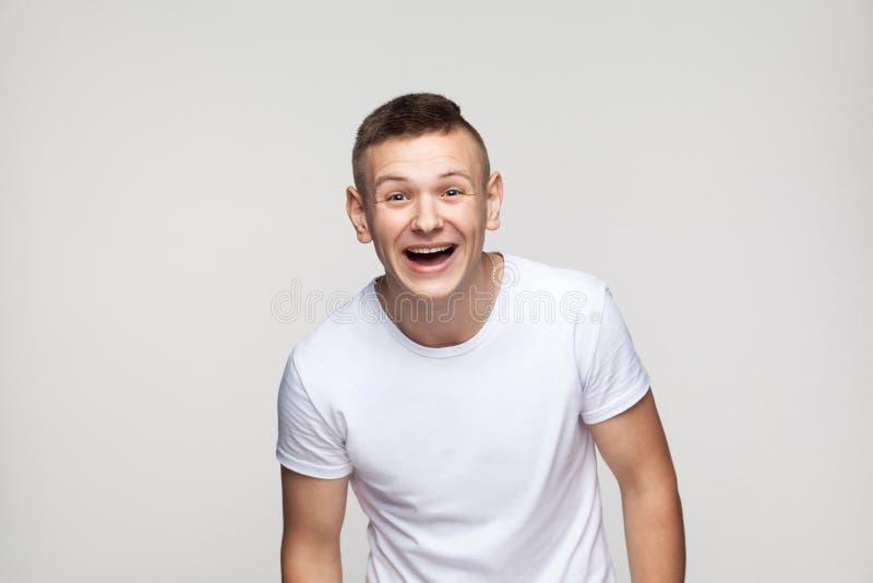 Homem novo do sucesso que olha a câmera e o sorriso toothy imagens de stock royalty free