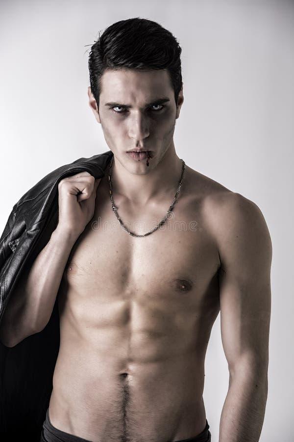 Homem novo do vampiro com o casaco de cabedal preto no ombro imagens de stock