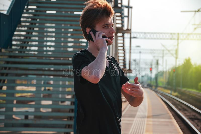Homem novo do viajante que fala através do telefone na estação de trem durante o tempo quente do verão, fazendo gestos ao falar imagens de stock