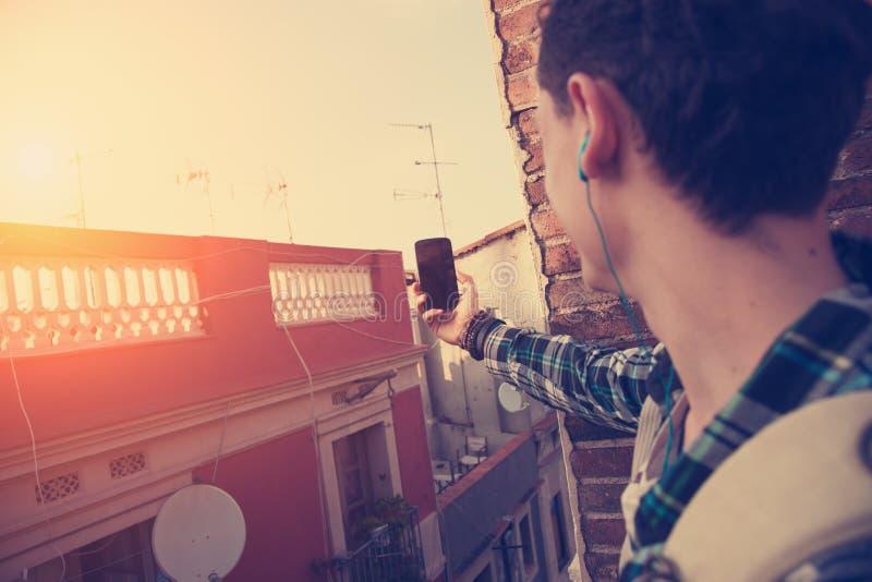 Homem novo do viajante que faz a foto com telefone celular no telhado imagem de stock