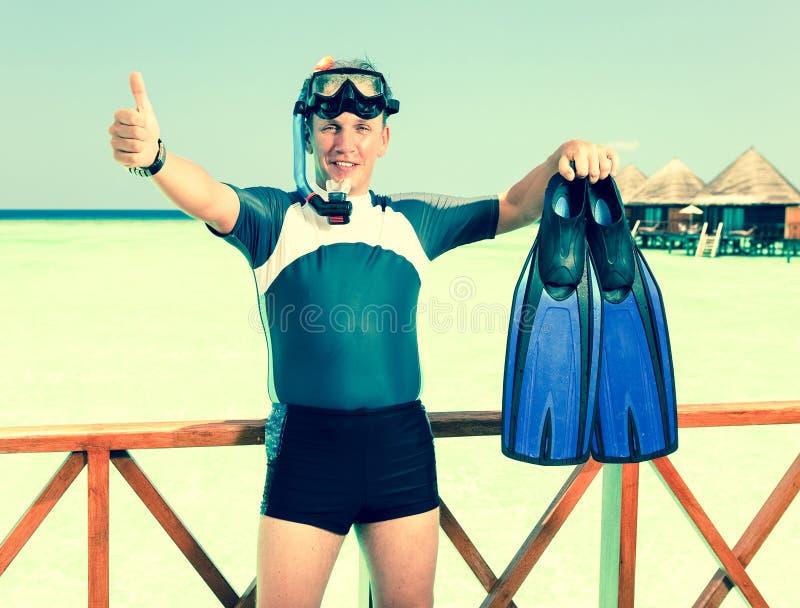 Homem novo dos esportes com aletas, máscara e câmara de ar perto do oceano foto de stock royalty free