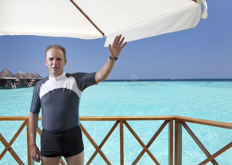 Homem novo dos esportes com aletas, máscara e tubo no sundeck de uma casa sobre o mar maldives imagens de stock royalty free