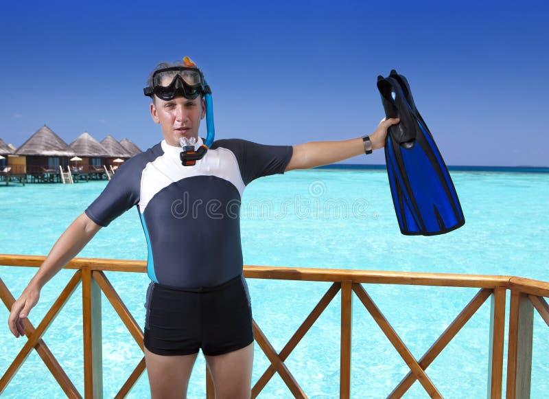 Homem novo dos esportes com aletas, máscara e tubo no sundeck de uma casa sobre o mar maldives imagem de stock