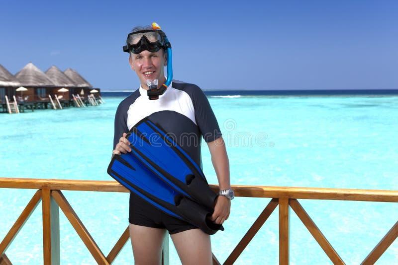 Homem novo dos esportes com aletas, máscara e tubo no sundeck de uma casa sobre o mar maldives fotos de stock