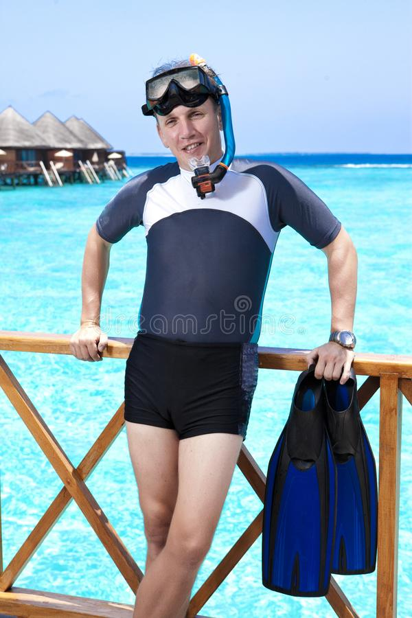 Homem novo dos esportes com aletas, máscara e tubo perto do mar maldives imagens de stock royalty free
