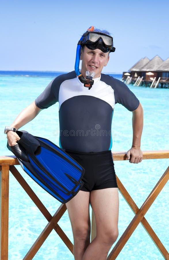 Homem novo dos esportes com aletas, máscara e tubo perto do mar maldives fotografia de stock