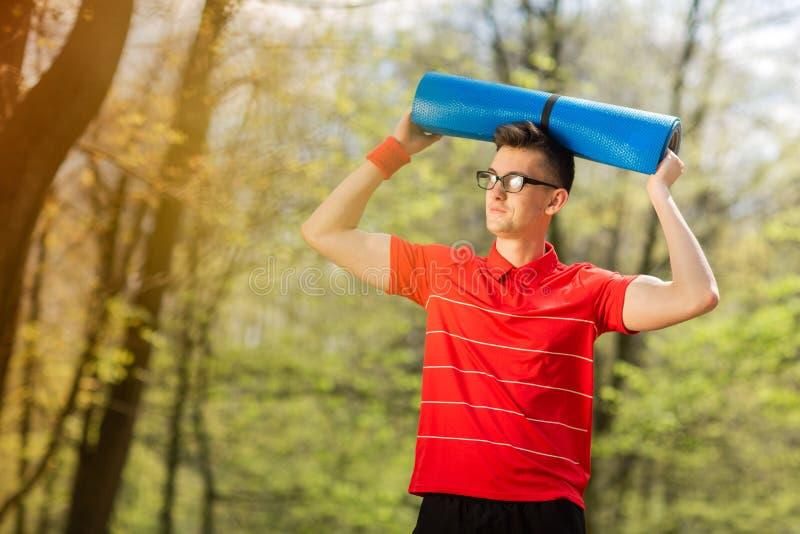 Homem novo dos esportes no t-shirt vermelho que levanta em um parque da mola com uma esteira azul da ioga Guarda uma esteira da i imagem de stock royalty free