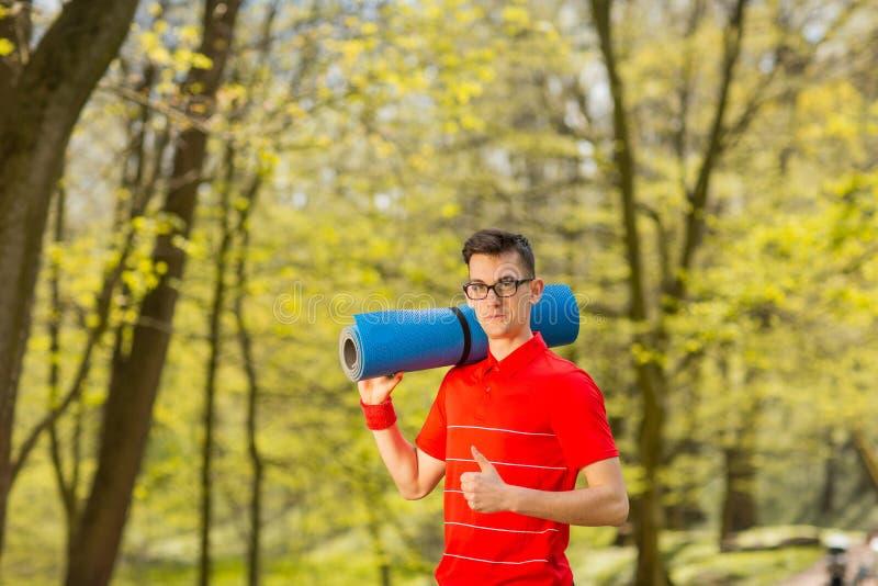 Homem novo dos esportes no t-shirt vermelho que levanta em um parque da mola com uma esteira azul da ioga Sua classe das mostras  imagem de stock