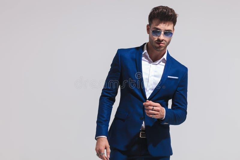 Homem novo dramático da forma no levantamento do terno e dos óculos de sol foto de stock