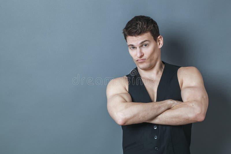 Homem novo duvidoso que mostra sua força muscular arrogante fotografia de stock